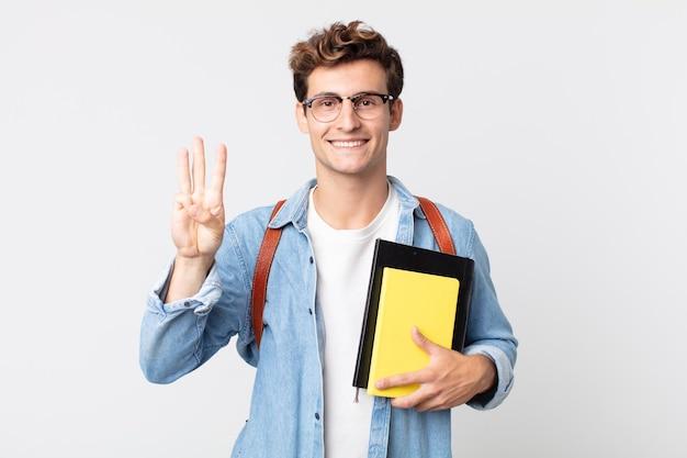 Jonge knappe man lacht en ziet er vriendelijk uit, met nummer drie. universitair studentenconcept