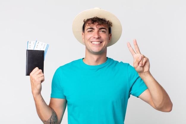 Jonge knappe man lacht en ziet er vriendelijk uit, met nummer twee. reiziger met zijn paspoort