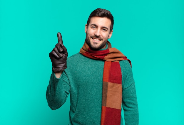 Jonge knappe man lacht en ziet er vriendelijk uit, nummer één of eerst met de hand naar voren, aftellend. koud en winterconcept
