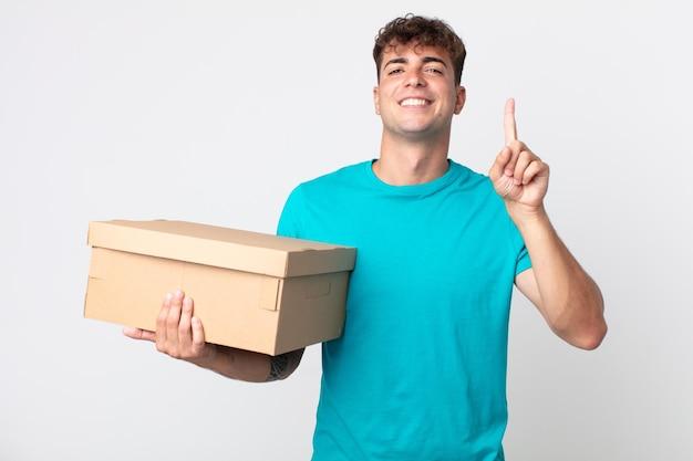 Jonge knappe man lacht en ziet er vriendelijk uit, toont nummer één en houdt een kartonnen doos vast