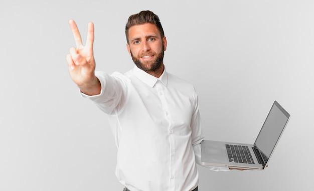 Jonge knappe man lacht en ziet er vriendelijk uit, toont nummer twee en houdt een laptop vast