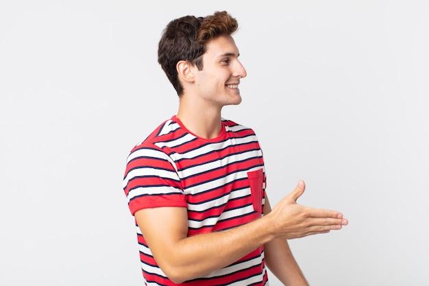 Jonge knappe man lacht, groet je en biedt een handdruk om een succesvolle deal te sluiten, samenwerkingsconcept