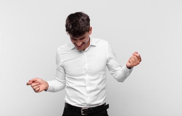 Jonge knappe man lacht, voelt zich zorgeloos, ontspannen en gelukkig, danst en luistert naar muziek, plezier op een feestje