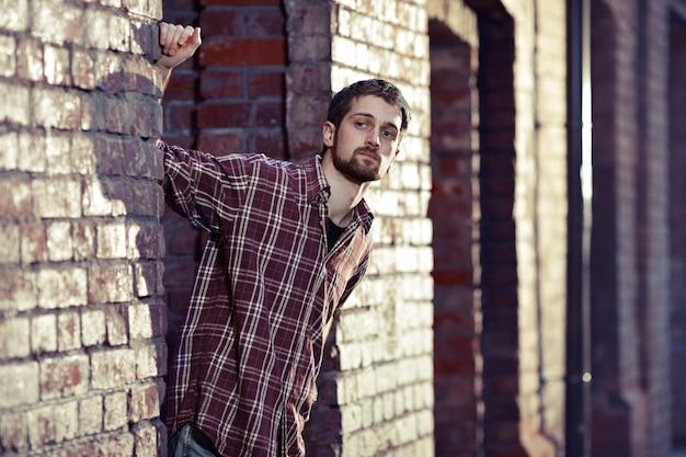Jonge knappe man leunde tegen de bakstenen muur en was op zoek naar iemand