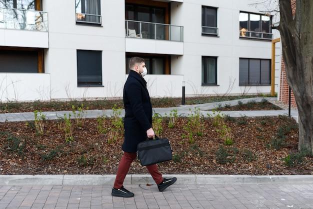 Jonge knappe man lopen in een woonwijk tijdens covid-19 coronavirus wereldwijde pandemie, in quarantaine met chirurgisch masker