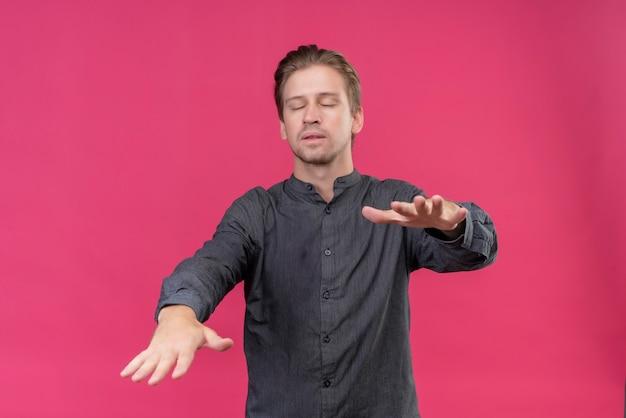 Jonge knappe man lopen met gesloten ogen stak zijn handen