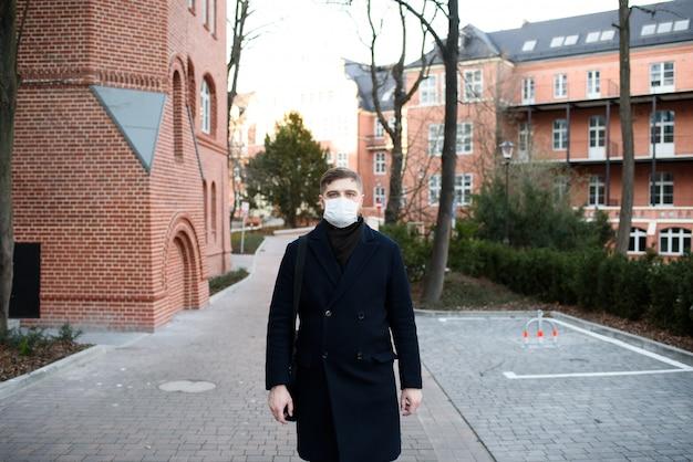 Jonge knappe man lopen met gezichtsmasker in een woonwijk tijdens covid-19 coronavirus wereldwijde pandemie en quarantaine