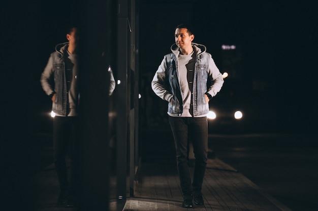 Jonge knappe man lopen 's avonds buiten de straat