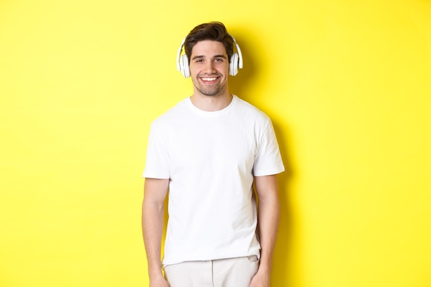 Jonge knappe man luisteren muziek in koptelefoon, oortelefoons dragen en glimlachen, staande op gele achtergrond.