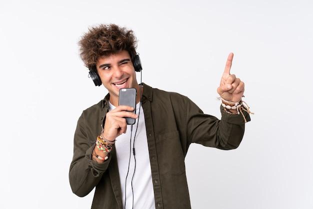 Jonge knappe man luisteren muziek met een mobiel over geïsoleerde muur