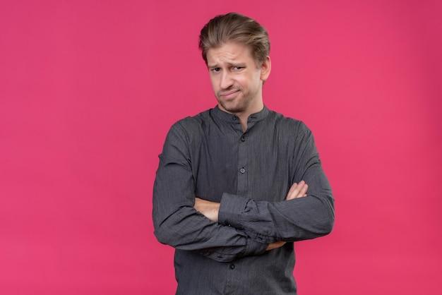 Jonge knappe man met armen gekruist met walgelijke uitdrukking staande over roze muur