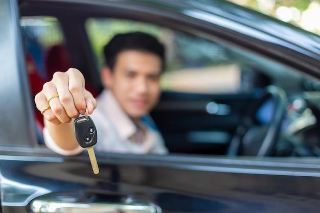 Jonge knappe man met auto sleutel afstandsbediening