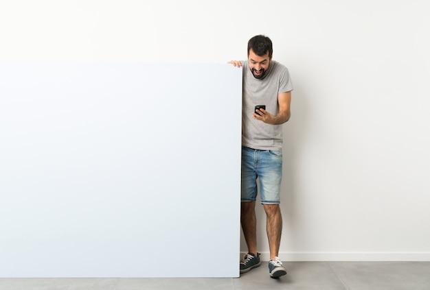 Jonge knappe man met baard die een groot blauw leeg aanplakbiljet houdt verrast en een bericht verzendt