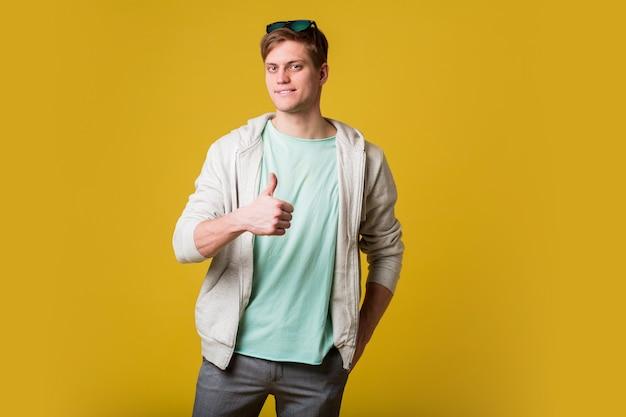 Jonge knappe man met baard die zich over gele muur bevindt die met gelukkig gezicht glimlacht en met omhoog duim naar de kant kijkt.