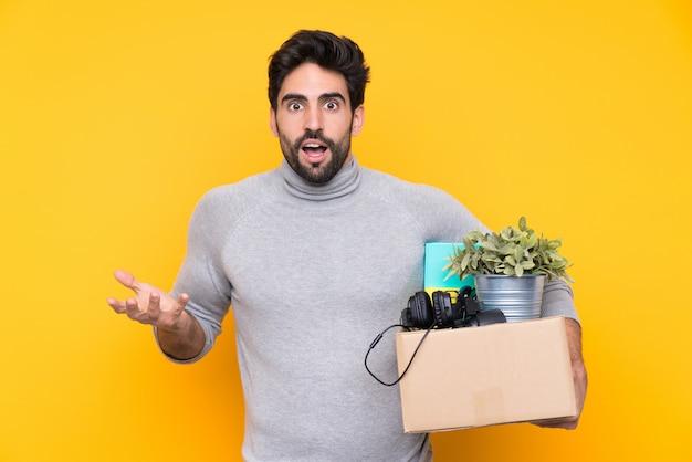 Jonge knappe man met baard een beweging maken terwijl het oppakken van een doos vol dingen over geïsoleerde muur met geschokte gelaatsuitdrukking