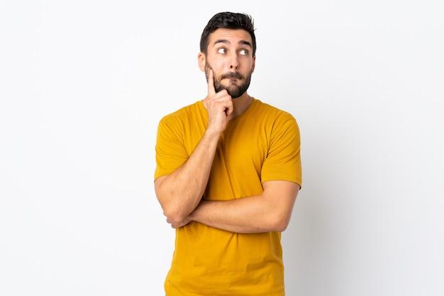Jonge knappe man met baard geïsoleerd op een witte muur met twijfels en denken