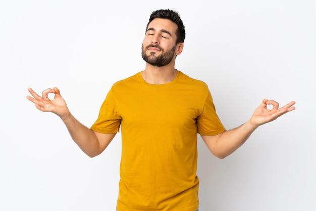 Jonge knappe man met baard geïsoleerd op wit in zen pose