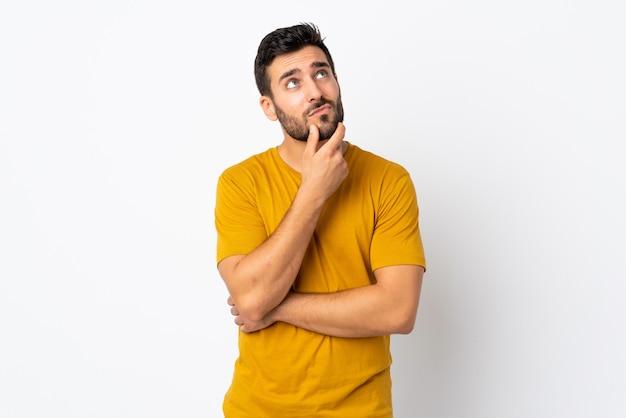 Jonge knappe man met baard geïsoleerd op wit met twijfels