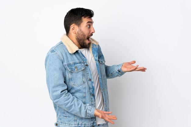 Jonge knappe man met baard geïsoleerd op wit met verrassing expressie terwijl op zoek kant