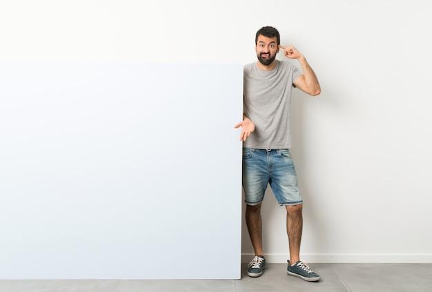 Jonge knappe man met baard met een groot blauw leeg plakkaat dat het gebaar van waanzin maakt die vinger op het hoofd zet