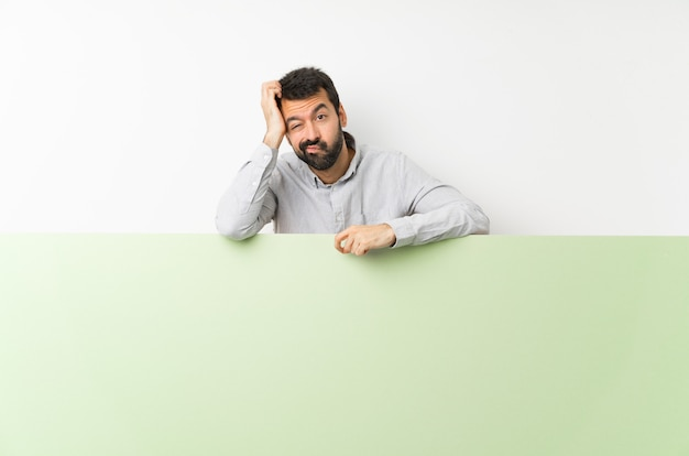 Jonge knappe man met baard met een groot groen leeg bordje met een uitdrukking van frustratie en niet begripvol