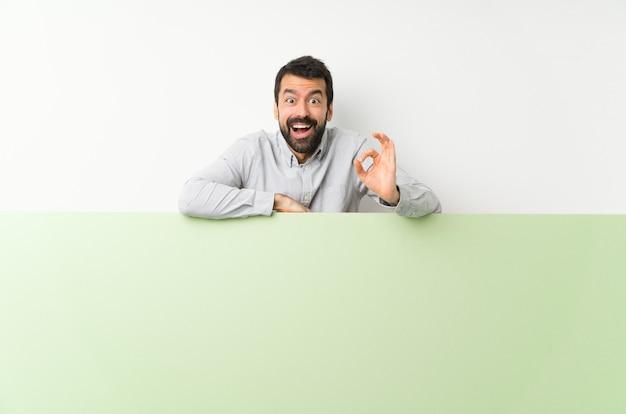 Jonge knappe man met baard met een groot groen leeg plakkaat verrast en het tonen van ok teken