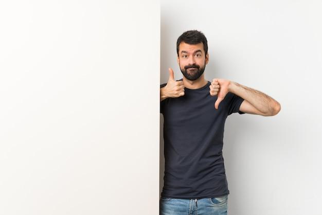 Jonge knappe man met baard met een groot leeg bordje maken goed-slecht teken. onbeslist tussen ja of niet
