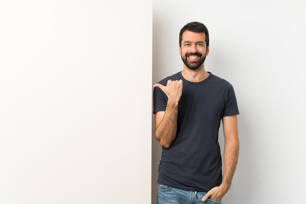 Jonge knappe man met baard met een groot leeg bordje naar de zijkant gericht om een product te presenteren