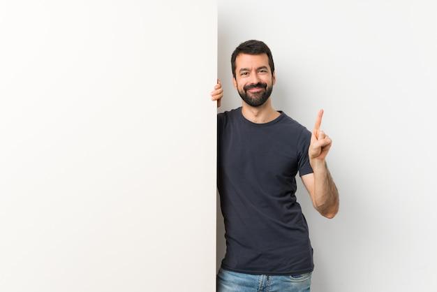 Jonge knappe man met baard met een groot leeg bordje tonen en het opheffen van een vinger in teken van de beste