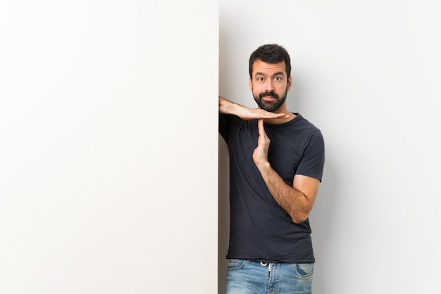 Jonge knappe man met baard met een groot leeg plakkaat maken time-out gebaar