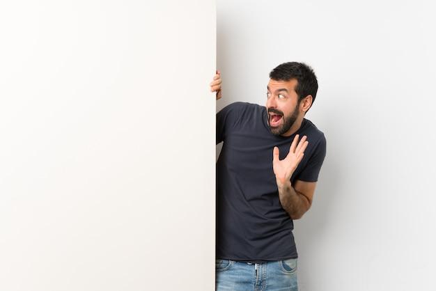 Jonge knappe man met baard nerveus en bang