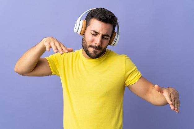 Jonge knappe man met baard op paarse muur luisteren muziek en dansen