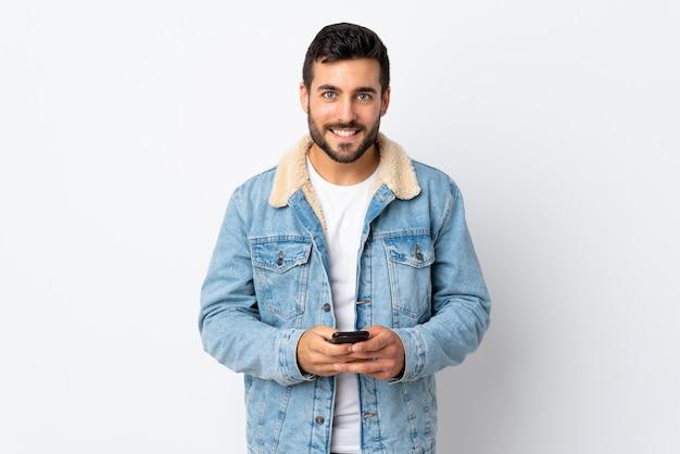 Jonge knappe man met baard op witte muur het verzenden van een bericht met de mobiele