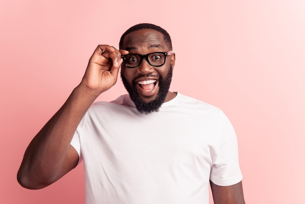 Jonge knappe man met baard opgewonden gezicht op roze achtergrond