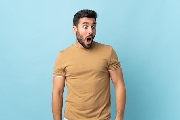 Jonge knappe man met baard over geïsoleerd doet verrassingsgebaar terwijl hij naar de zijkant kijkt