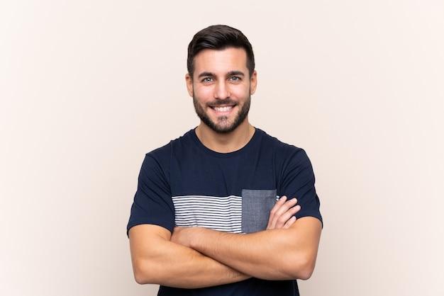 Jonge knappe man met baard over geïsoleerd houden de armen gekruist in frontale positie