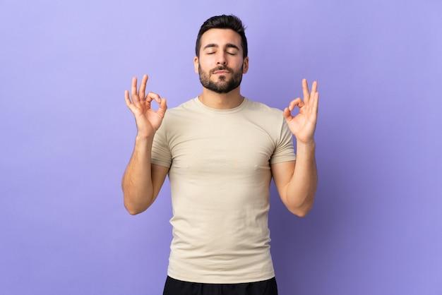 Jonge knappe man met baard over geïsoleerd in zen pose