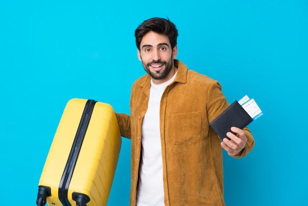 Jonge knappe man met baard over geïsoleerde blauwe muur in vakantie met koffer en paspoort