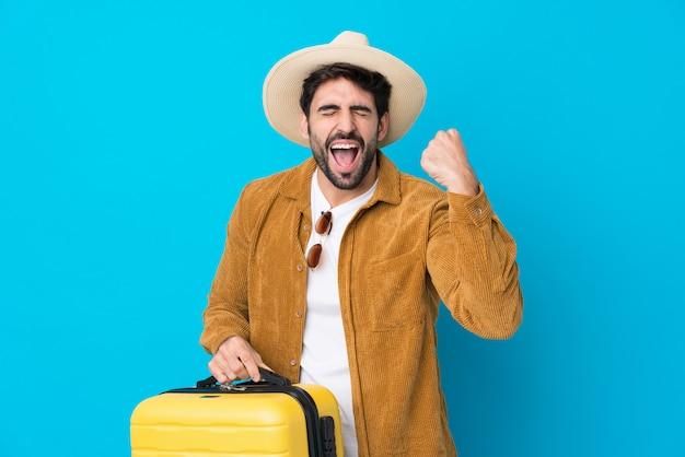Jonge knappe man met baard over geïsoleerde blauwe muur in vakantie met reiskoffer en een hoed