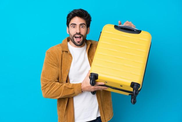 Jonge knappe man met baard over geïsoleerde blauwe muur in vakantie met reiskoffer