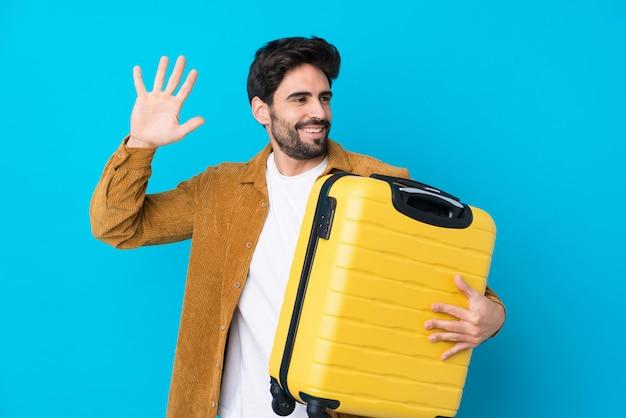 Jonge knappe man met baard over geïsoleerde blauwe muur in vakantie met reizen koffer en groeten