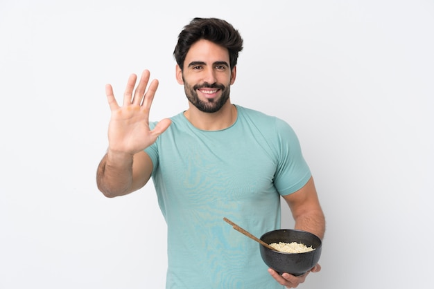 Jonge knappe man met baard over geïsoleerde witte muur die met hand met gelukkige uitdrukking groeten terwijl het houden van een kom van noedels met eetstokjes