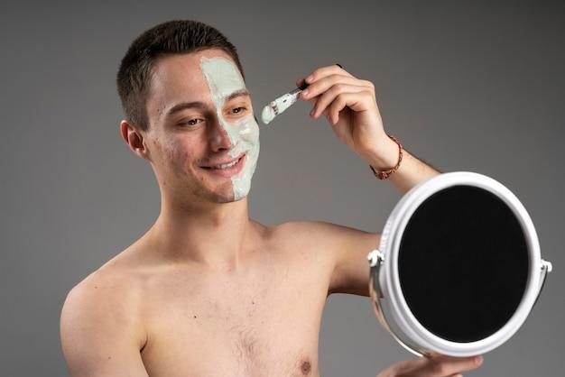 Jonge knappe man met behulp van een masker voor acne