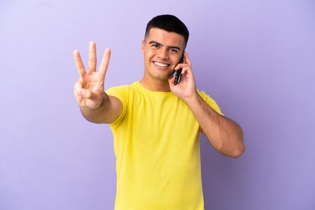 Jonge knappe man met behulp van mobiele telefoon over geïsoleerde paarse achtergrond gelukkig en drie tellen met vingers