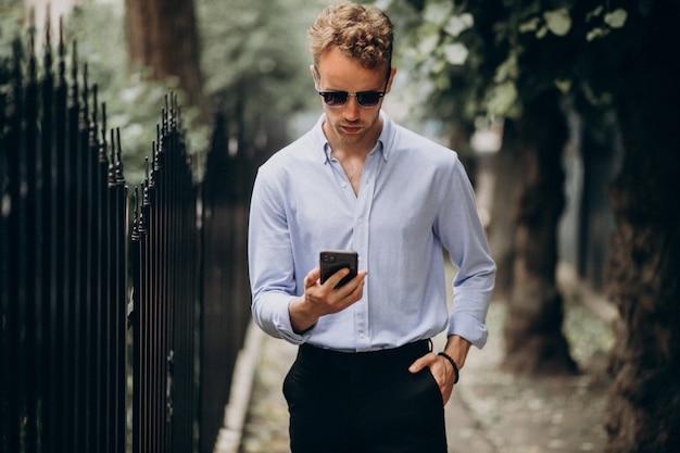 Jonge knappe man met behulp van telefoon in de straat