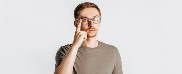 Jonge knappe man met bril denkt op geïsoleerde grijze achtergrond
