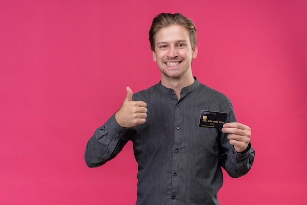 Jonge knappe man met creditcard duimen opdagen, glimlachend staande over roze muur