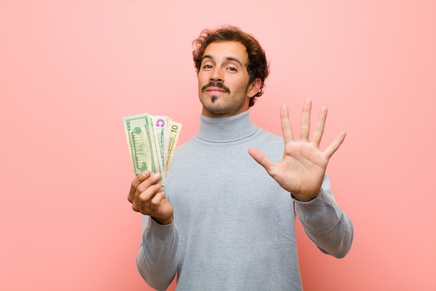 Jonge knappe man met dollarbankbiljetten tegen roze vlakke muur