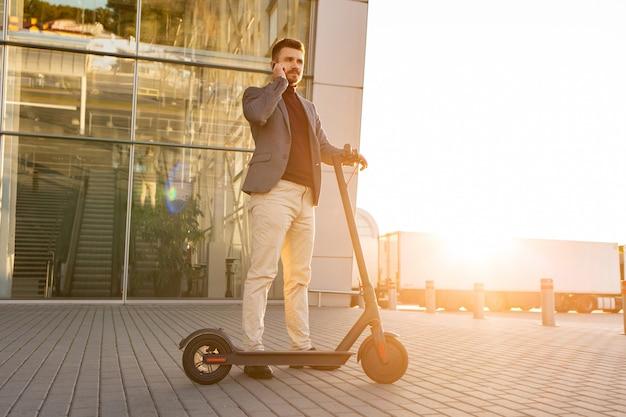Jonge knappe man met e-scooter staande op de stoep in de buurt van de luchthaven op de zonsondergang en praten op de smartphone