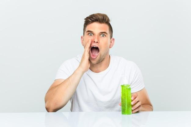 Jonge knappe man met een aloë vera fles schreeuwen opgewonden aan de voorkant.